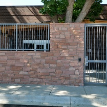 "Iron ""Tree Bark"" style fencing and security gate mounted around rock. Loveland, CO"